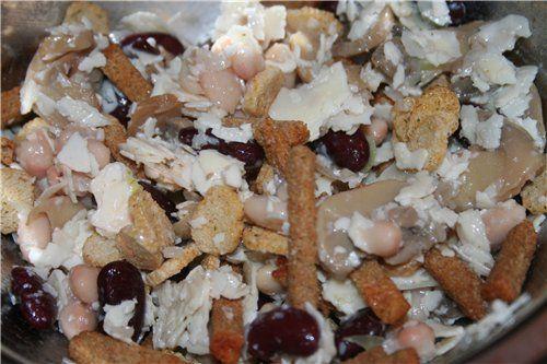 Салат из фасоли с чесночными сухариками Консервированная красная фасоль – 1 банка, сладкий красный перец – 1 шт, твердый сыр – 150 гр, варено-копченая ветчина – 150 гр,  лук-порей – 1 шт, ржаной хлеб - 150 гр, растительное масло – 100гр, зубчик свежего чеснока, сухой базилик и соль - по вкусу.