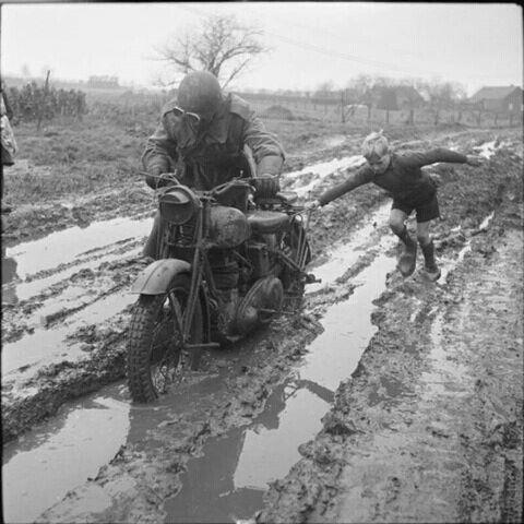 Голландский мальчик помогает выбраться из грязи британскому военному почтальону, Голландия, 11 декабря 1944 года.