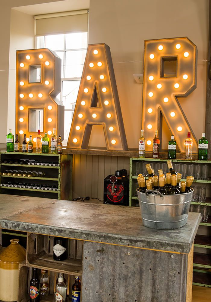 We LOVE these light up bar lights to define your reception space, especially if it's in a room without a drinks area usually like a village hall! High ceilings with these top decor tips makes for a chic hall reception venue • Find out how to style your dream wedding on the Wedding Ideas website!