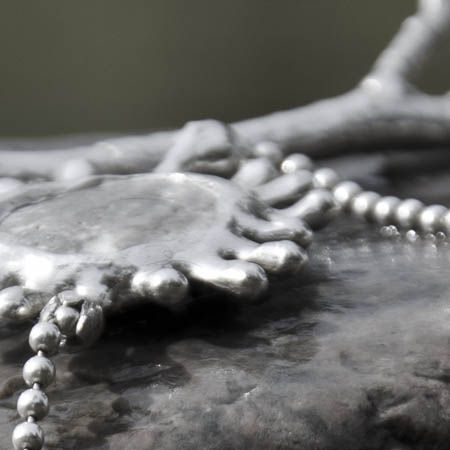 Detail neckless with hand casted branch, silver inlaid beach stone and a fresh water pearl.