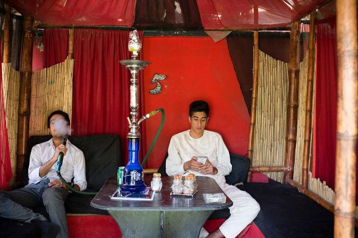Young Afghan men, all in their early 20s, socialize and smoke hooka at Cafe Che, in Western Kabul. Cafe Che is one of the fewer cafes that have become very popular among young people in mixed groups as a meeting place. Kabul, Afghanistan, Aug. 10, 2014.