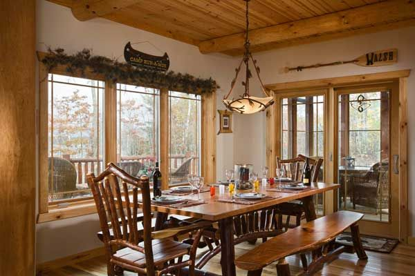 A cedar base and cherry top form this rustic-style dining room set, fitting perfectly with Judi's North Woods decor. The pinecone metal chandelier complements the pot rack in the adjacent kitchen. Judi opted for pinecones and evergreen branches instead of drapes to preserve the view.