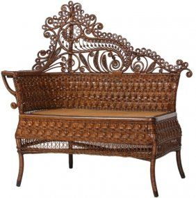 Love the rich color and crisp details on this Victorian wicker photographer's bench. The ornate natural wicker bench has a high fancy scrolling crest on the curved back, one arm on the side with a corbel support and open apron below on crescent legs. 42 in. high x 41 in. wide x 18 in. deep