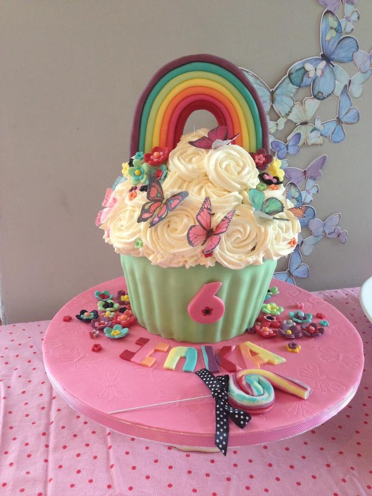 Flowers, butterflies and rainbow. The most beautiful birthday cake. Rainbow giant cupcake with rainbow cake inside.