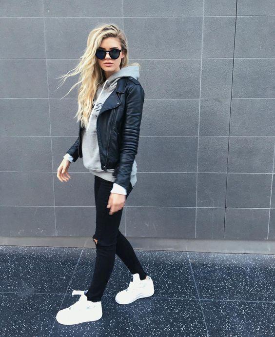 8 Ideias de looks para testar antes que o inverno termine. Jaqueta de couro, moletom cinza, calça preta com rasgo no joelho, tênis branco.