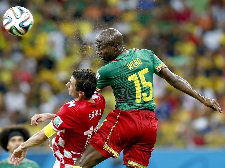 Pierre Webo dos Camarões (R) Darijo Srna da Croácia (2R) saltar para um cabeçalho durante o 2014 FIFA World Cup grupo A partida preliminar e volta entre Camarões e pela Croácia na Amazônia Arena em Manaus, Brasil