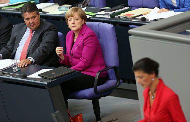 Bundeskanzlerin Angela Merkel (CDU) (m), Vizekanzler Sigmar Gabriel (SPD) (l) und Sahra Wagenknecht (Die Linken) am Rednerpult, am 14. Juni 2014 im Bundestag. Foto: Adam Berry/Getty Images