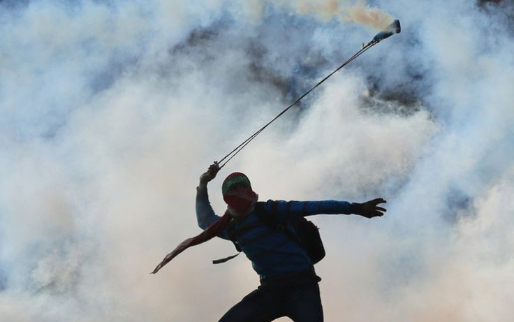 A masked Palestinian youth wearing a Hamas headband uses a sling-shot to throw back a tear gas canister towards Israeli forces during clashes outside the Israeli-run Ofer military prison, near the West Bank city of Ramallah