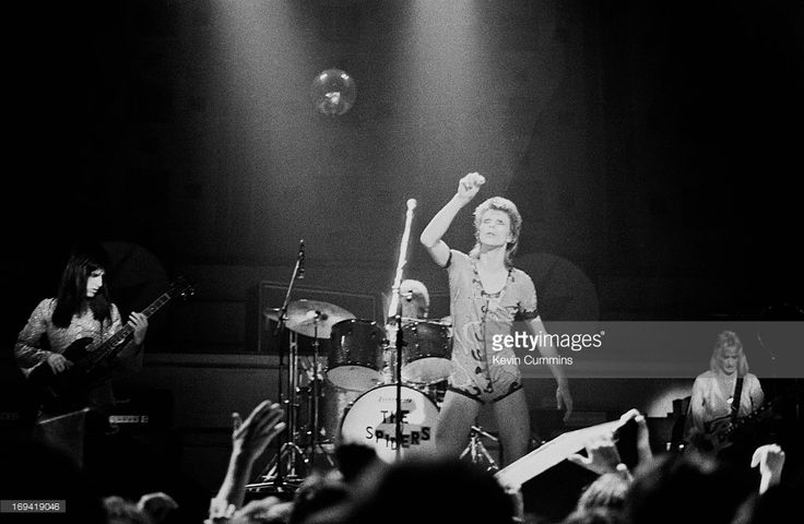 English singer David Bowie performs on stage with bass player Trevor Bolder (left), drummer Mick 'Woody' Woodmansey (centre), and guitarist Mick Ronson (right) at Free Trade Hall in Manchester as part of the Ziggy Stardust / Aladdin Sane tour on June 7th, 1973.