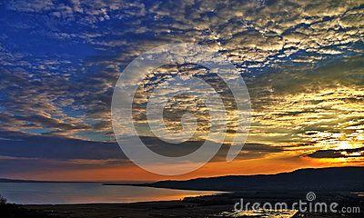 panorama del tramonto spettacolare sopra il Balaton in Ungheria Le nuvole sembrano disegnare un cerchio nel centro di cui nasconde il sole I colori del cielo sono riflessi nell'acqua del lago