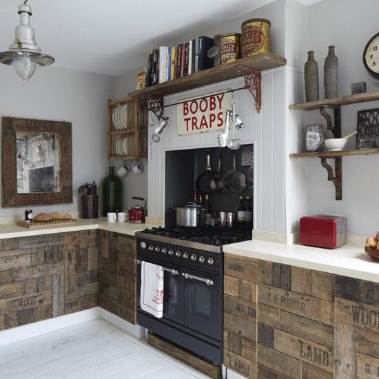 Rustic kitchen - tongue and groove white walls, black Britannia range cooker, wood shelves with rusty shelf brackets, black station clock, grocery box kitchen doors, red toaster & kettle,  wall hung plate rack white plates, mugs, wood mirror, white floorboards, cream worktop