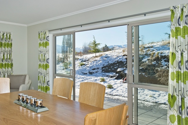 Crisp white curtains with green accents and a natural timber dining suite invite the outdoors inside in this alpine home.