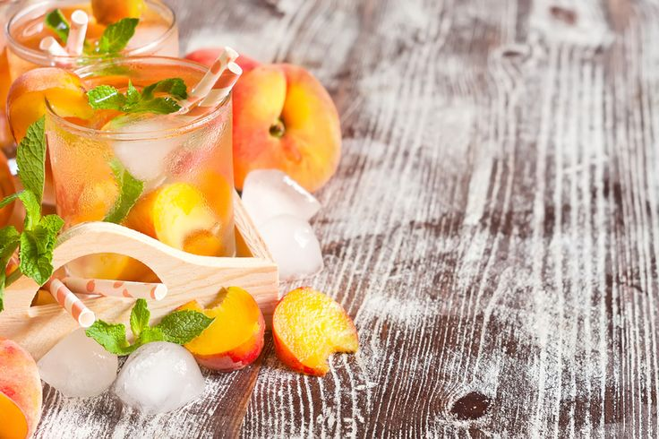 Homemade lemonade with ripe flat saturn-shaped peaches and fresh mint. Copy space background.
