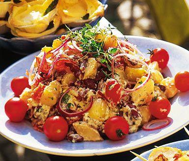 En uppiggande variant på potatissallad finner du i detta recept. Grunden består av nykokta potatisar, röda bönor, krispig lök och tomater som du blandar med en krämig sås av pesto och crème fraiche. Den kommer garanterat bli uppskattad!