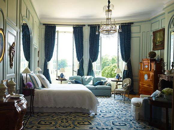 Each of the 14 bedrooms in Timothy Corrigan's 18th-century Loire Valley estate Château du Grand-Lucé reflects a distinct design sensibility. This blue-gray guest room includes an antique Portuguese rug, an 18th-century Swedish chandelier, a pair of 19th-century British side tables and a Louis XVI chair.