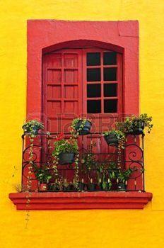 smeedijzer%3A+Rood+gelakt+venster+met+planten+en+smeedijzeren+leuning+in+Mexico+