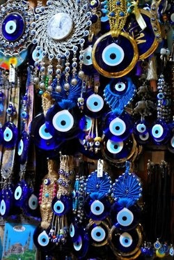 """Belief in the evil eye is strongest in the Middle East, Asia and Europe.  In some areas where light-colored eyes are relatively rare, people with blue eyes are feared to possess the power to bestow the curse, intentionally or not.  Belief in the evil eye features in Islamic folk religion and Jewish folklore.  In Latin, the evil eye was fascinum, the origin of the English word """"to fascinate"""". The evil eye belief spread to northern Europe, especially the Celtic regions."""