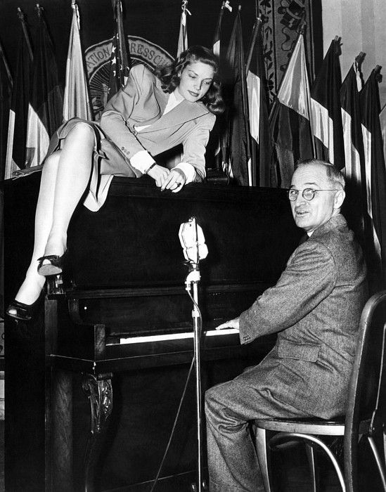 Actress Lauren Bacall sits atop the piano while Vice President Harry Truman plays. The iconic photo was taken at the National Press Club Canteen, where Bacall and the Vice President entertained American servicemen. Feb. 10, 1945. (CSU_ALPHA_212) CSU Archives/Everett Collection