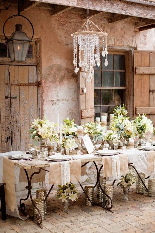 Beautiful table setting against the rustic dwelling  With large comfy chairs