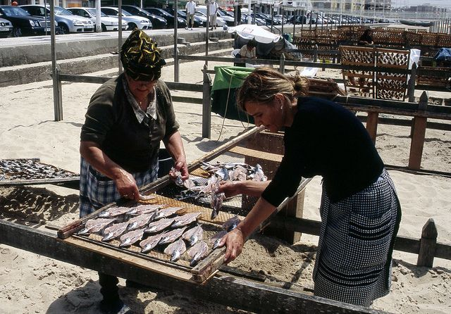 the ladies of Nazaré in Western Portugal wear traditional dress a plaid apron and colourful head scarves.  They dry the fish their husbands catch in the sun on the beach slap bang in the middle of the town.