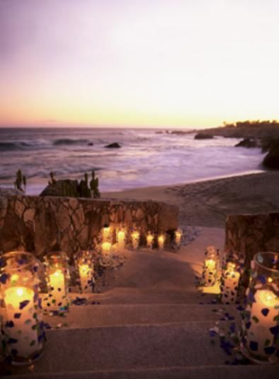 Candles or luminaries leading down the beach at sunset.  I really like this!
