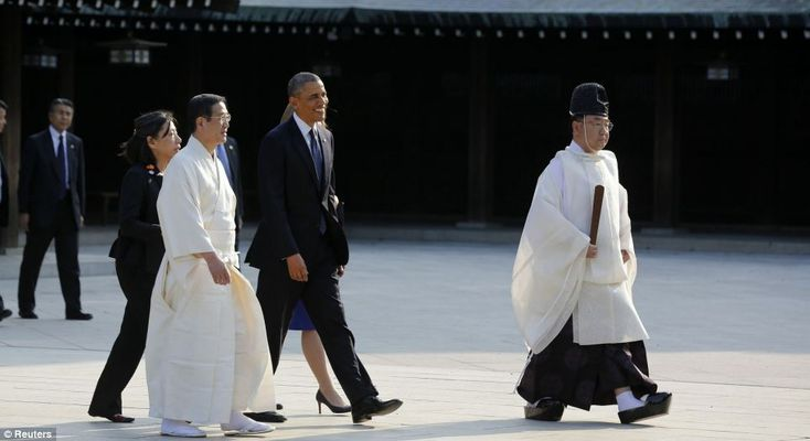 Mr Obama walks with senior priest Hiroyasu Nukaga, second left, and chief priest Seitaro Nakajima on a visit to the Meiji Shrine