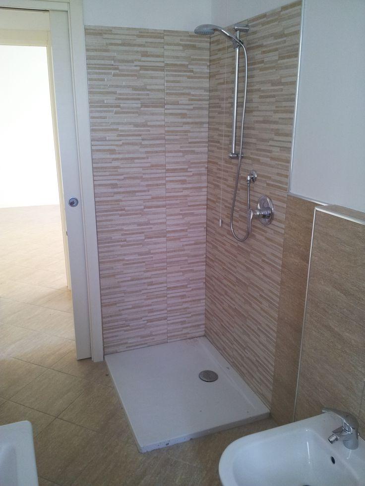 Dettaglio doccia ove si nota il tutt'uno del pavimento bagno con pavimento esterno dell'appartamento ed i profili in acciaio.