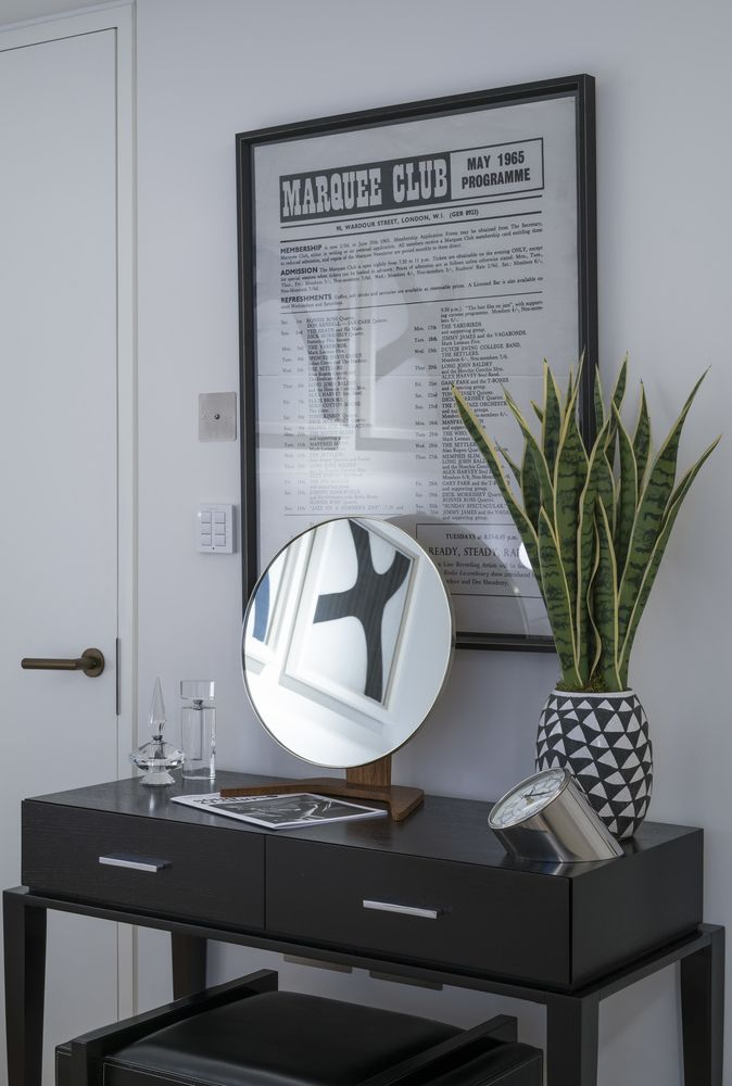 This refined chocolate oak console table paired with a black leather stool adds traditional elegance to the light, contemporary bedroom; brought to life by the vibrant pot plant greenery and completed by the stylish bespoke rounded mirror. #interiordesign #luxurylife #luxury #london #luxuryproperty #luxuryhomes #londonproperty #luxuryinteriors