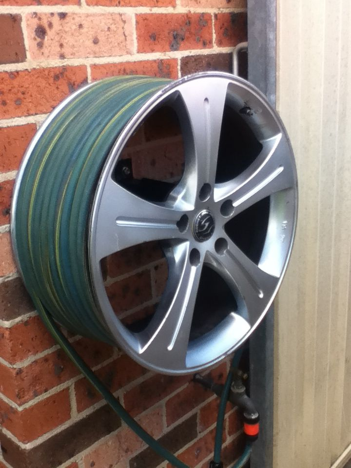 Outside the man cave... The only good use for a Holden wheel, a hose reel