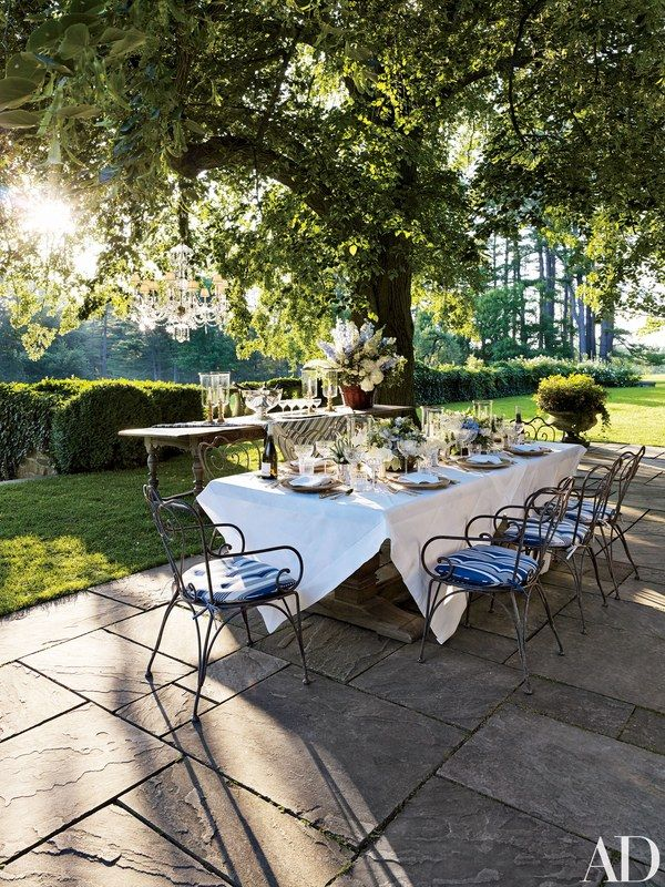 On a terrace shaded by a linden tree, vintage wrought-iron chairs encircle a table set for an alfresco dinner; the striped cushions, tableware, and chandelier are by Ralph Lauren Home | archdigest.com