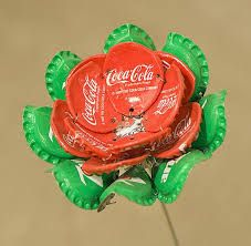 A good way too use bottle lids again.          To stick them together use a strong glue and as a stem use anything strong enough