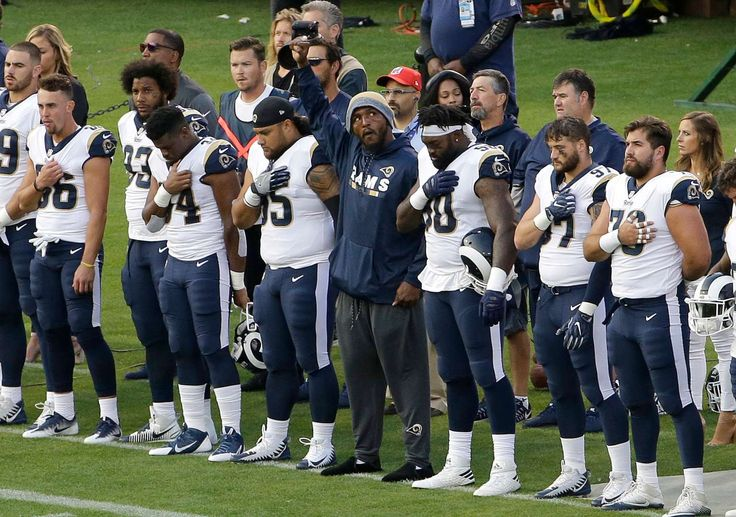 NFL players' national anthem protests   -  Los Angeles Rams linebacker Robert Quinn, center, raises his fist during the national anthem before a preseason game against the Oakland Raiders in Oakland, Saturday, Aug. 19, 2017.