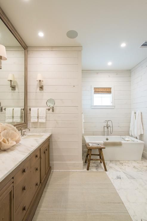 White and brown bathroom features a bathtub nook equipped with a freestanding bathtub paired with a polished nickel tub filler positioned beneath a window framed by shiplap trim and dressed in a bamboo roman shade.