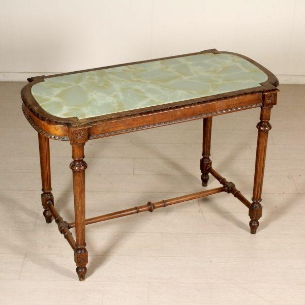 Tavolino Liberty da centro retto da gambe tornite raccordate da crociera. Piano sagomato con piano in onice incassato. Intagli.
