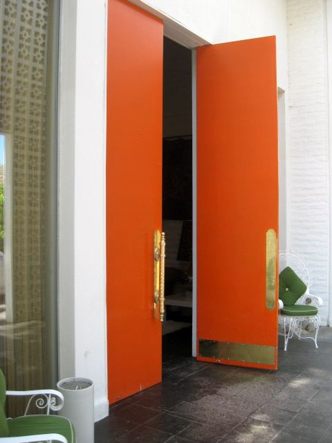 Entry doors in the color of the season! tangerine tango + brass kickplates and long handles