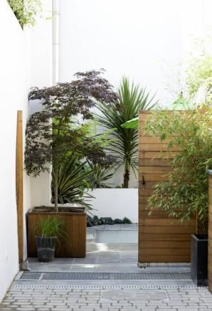 patio with grey paving and white rendered raised wall