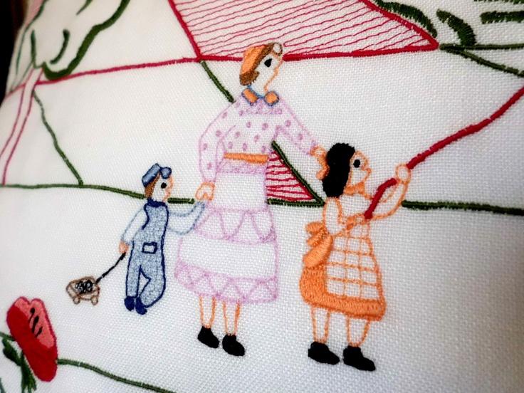 Detalle de madre con hijos de un bordado sobre un cojín de cama con fondo en tela blanca