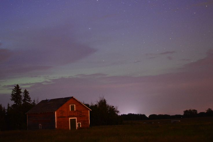 A barn in the night. The glow of the northern aurora in the background. The front of the barn is lit by cloud reflections of light pollution from Edmonton, 40 km away...