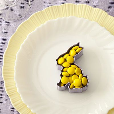 Place a bunny-or chick-shaped cookie cutter on a plate and fill it with M's in a single color. Provide guests with a small cellophane bag and a twist tie so they can take their candy home.