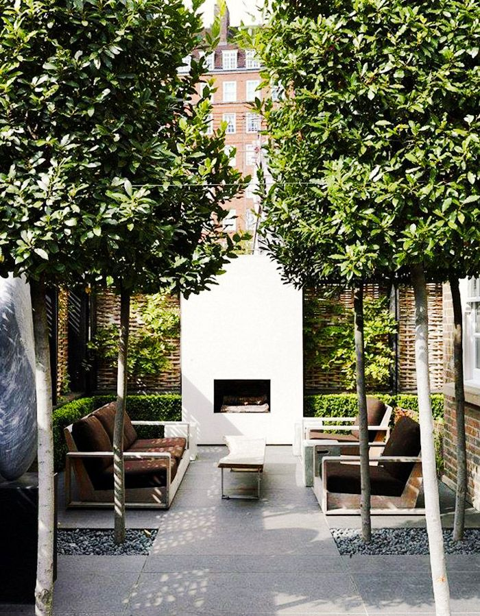 Modern white fireplace in outdoor sitting area with trees