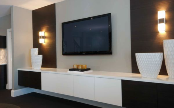 TV wall with floating storage cabinet and light sconces on a textures background