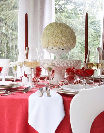 """Red-and-White Table:     """"A tall, stacked centerpiece is pretty when guests arrive. When they are seated, move the top and use the base for bread.""""    Vintage hobnail milk glass goblets, salad plates, and flatware, eddieross.com. 12"""" tapers, creativecandles.com."""