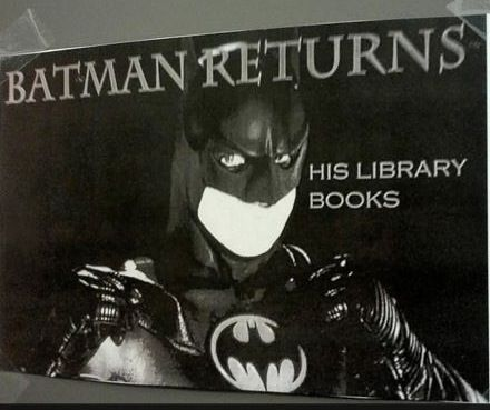 Batman reads and turns in his library books