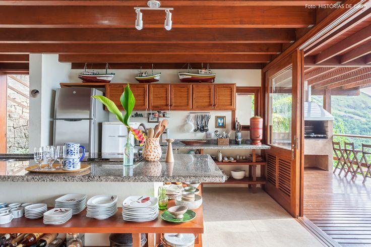 Cozinha de casa de praia tem bancada de granito e prateleiras abertas para guardar as louças.