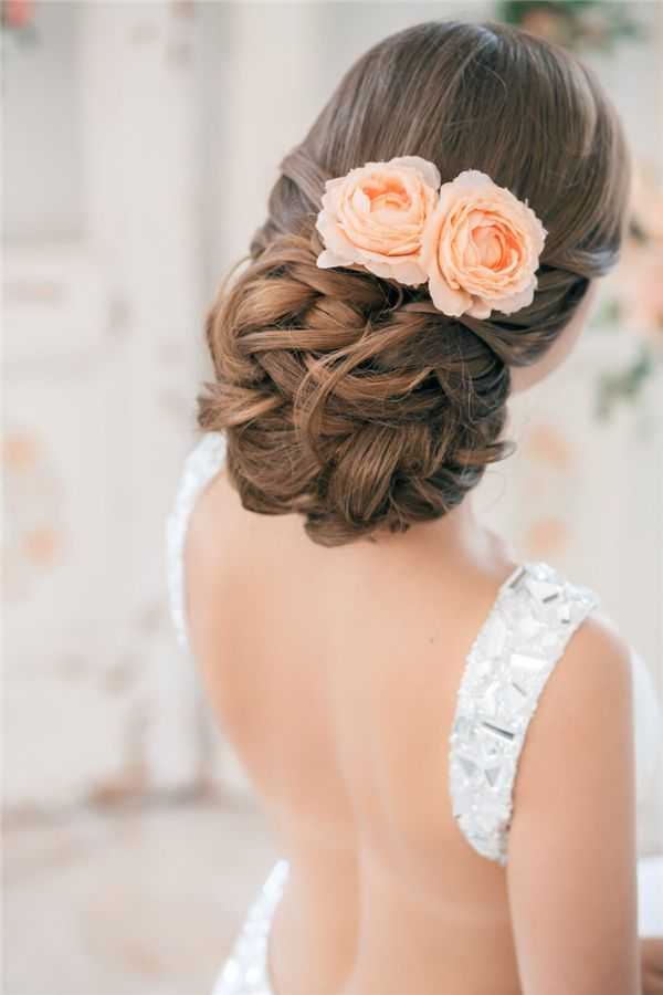 messy low updo hairstyle with coral roses…