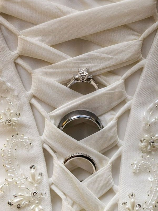 Love how this unique photo shows off the rings and the intricate details of the wedding gown at the same time!