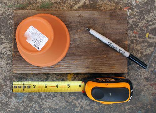 Measure and mark the plank of wood to create a square. Đo đạc và đánh dấu miếng gỗ để có 1 miếng vuông chứa được chiếc chậu.