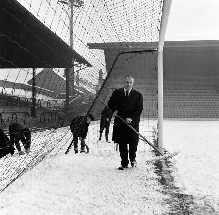 Bill Shankly helps to clear the snow from the goal line on the Anfield pitch as they prepare for the upcoming fixture against Sunderland. 28th December 1964.