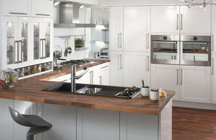 White Cabinetry With Hardwood Countertop With Panel Appliances ...