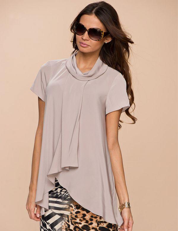 Эффектная блузка свободного покроя выполнена в нежной однотонной расцветке. Декоративные складки создают романтичный образ.